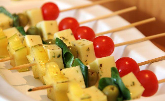 Espetinho com queijo muzzarela, azeitona, tomate cereja, carambola e folha de manjericão. Azeite o orégano para temperar o queijo.