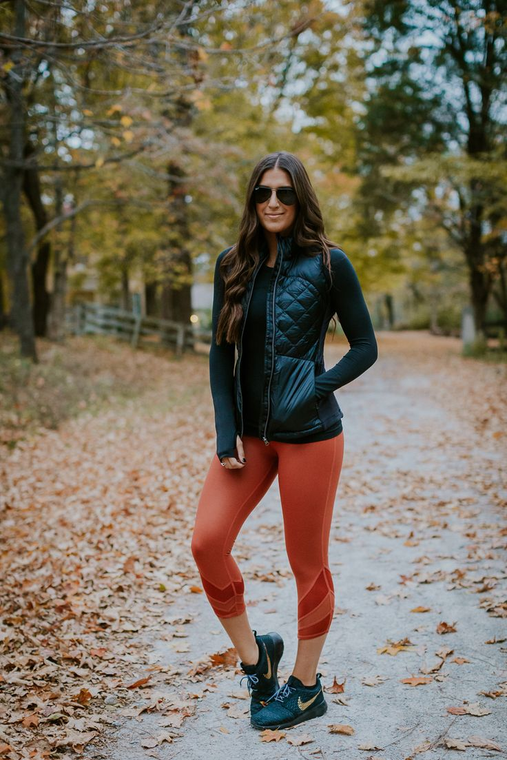 Weekly Workout Routine: Athletic Puffer Vest | A Southern Drawl. Black long sleeved tee+orange leggins+blue sneakers+black athletic puffer vest+sunglasses. Fall Workout Outfit 2016