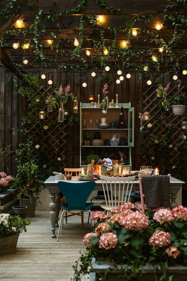 Backyard With Canopy Of Twinkle Lights And Wooden Dining Table Mismatched Chairs Pink Flowers