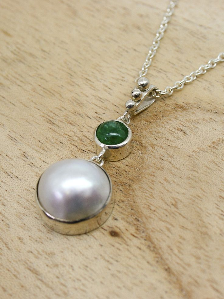 A beautiful necklace with a mabe pearl and cabochon emerald pendant in hallmarked sterling silver which has been created entirely by hand in our own workshop in St. Ives Cornwall. The pearl measures 14mm in diameter approx. and the emerald measures 6.5mm approx. both are mounted in silver with beaded pendant loop and 16 or 18 inch sterling silver trace chain.  #emerald #necklace #pearl #pendant #silver