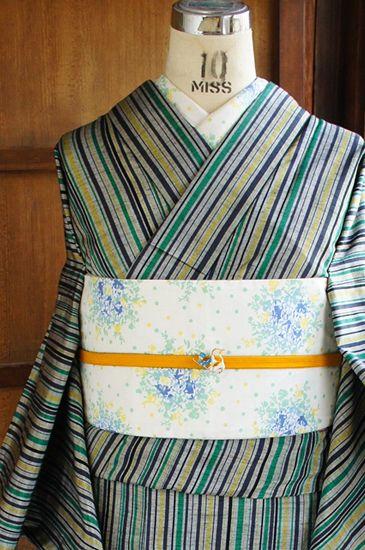 グレーの地に、緑と黄色と黒のストライプが織り出された正絹紬の単着物です。