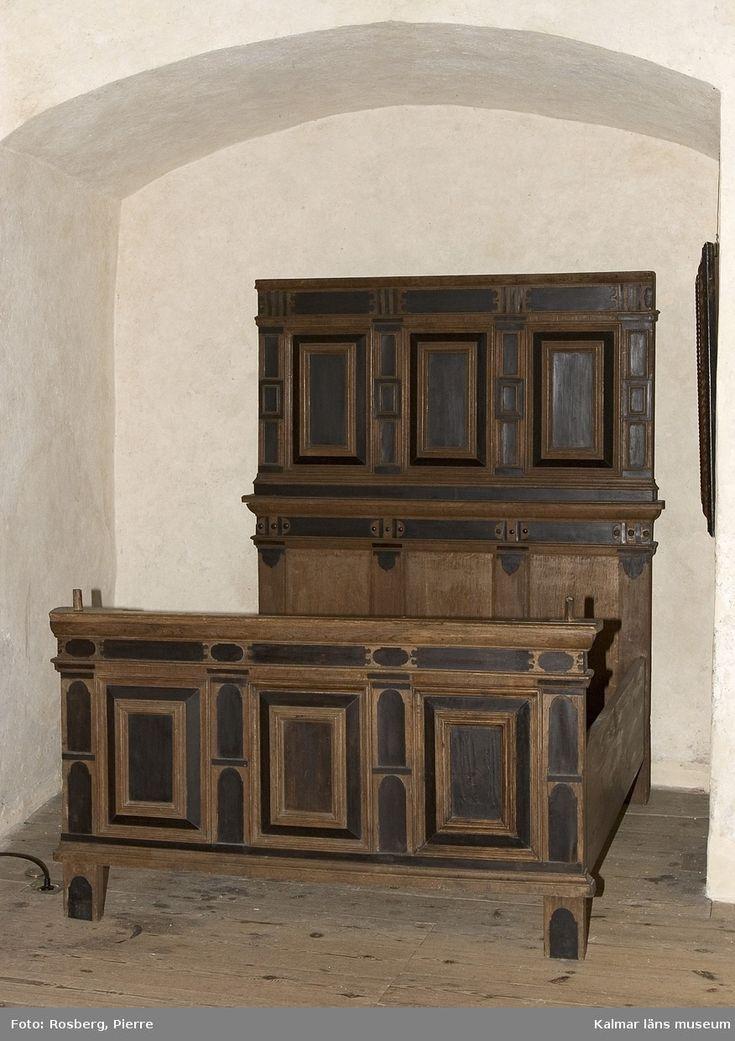 """KLM 17916. Säng tillverkad av trä, ek. Gavlarna hör till säng från 1600-talets mitt. Högre bakgavel bestående av två delar. Den övre fästs med triangelformade pinnar som träs igenom likformade hål i den undre gaveldelen. Lägre fotgavel som har haft svarvade stolpar i hörnen. Nu syns endast pluggar för infästning. Gavlarna är dekorerade med speglar och fyllningar """"färgade"""" med ekens naturfärg samt svarta detaljer. Ursprungliga långsidorna saknas. Renässans."""