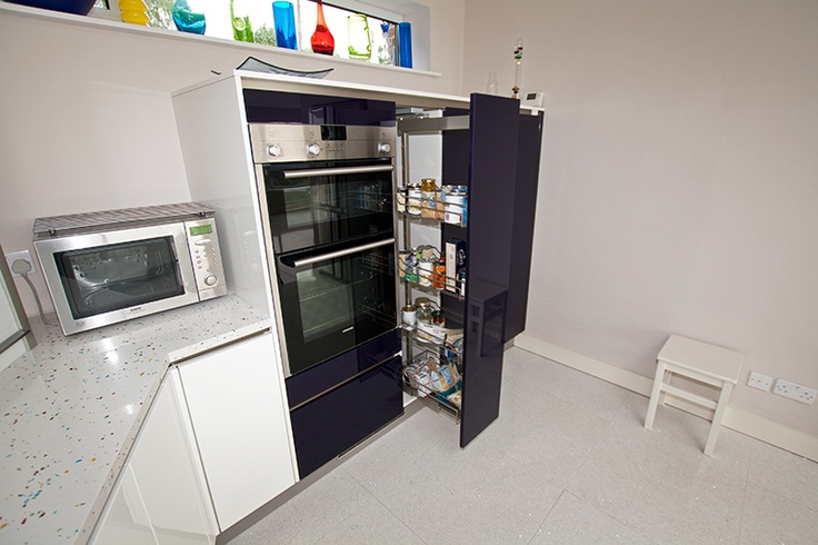 This blackberry design glass is nicely complimented with a colourful tutti-frutti worktop, as well as multi-coloured  ornaments, the combination of which brings an energetic sense of 'fun' to the kitchen design.  The pull out larder is an effective storage solution and even when extended the highly reflective gloss glass surface of the finish is plain to see.