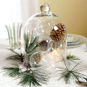 Nature is the muse for this glowing centerpiece. Fill a glass cloche with clear ornaments (with their caps removed) along with shapely pinecones and evergreen tips. Flip the cloche upside down on a paper plate, place on the table, and remove the paper plate. Surround the cloche with more evergreens for a fresh, fragrant display.