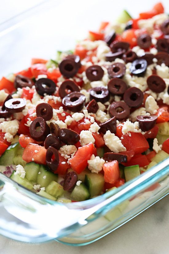 Hummus, yogurt, red onion, cucumbers, tomatoes, feta and olives are layered to create this delicious Greek inspired dip – grab a chip and serve this at your next party!  You can prep all the ingredients ahead, but it's best to layer it just before serving as the cucumbers tend to get watery if they sit too long. If you don't eat dairy, or if you want to keep it vegan, skip the yogurt and add more hummus!    Greek 7 Layer Dip Skinnytaste.com  Servings: 9 • Serving Size: 1/4 cup • Points : 3…