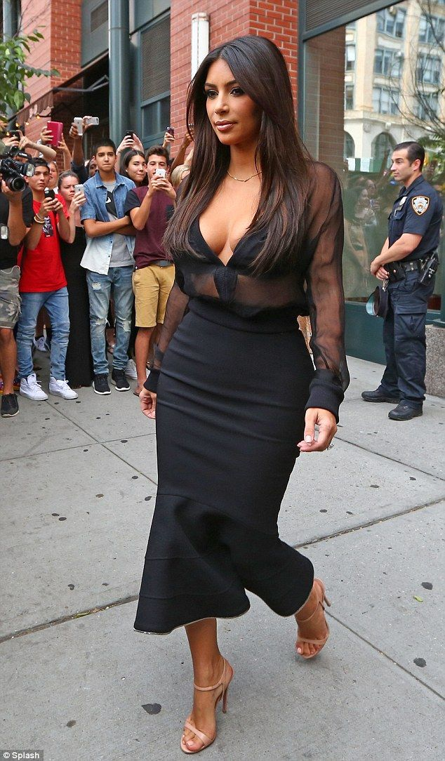 Kim Kardashian is a femme fatale in plunging blouse and fishtail skirt