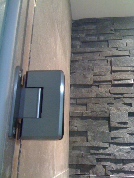 Stacked norstone tile with travertine walls and frameless glass shower