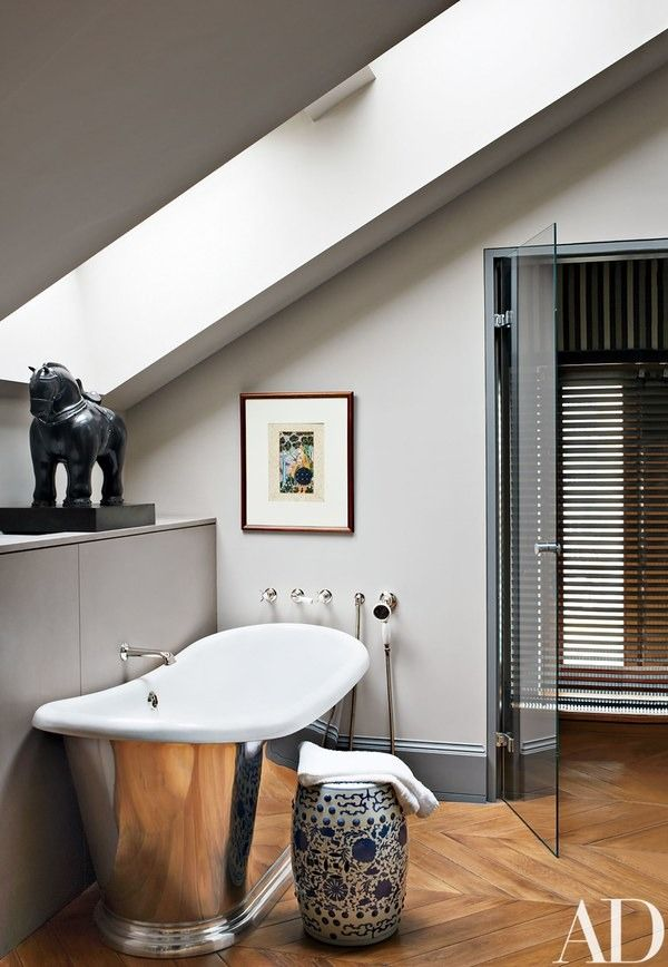 In the same room, the bath's tub fittings are by Lefroy Brooks; the horse sculpture is by Fernando Botero | archdigest.com