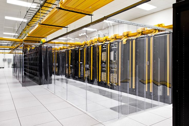 Plastic curtains hang in a network room of the data center. Cold air is served through the floor, and the clear plastic barriers help keep the cold air in while keeping hot air out.