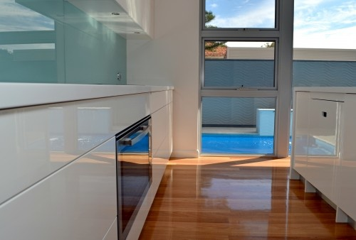 The glass back splash complements the cool color of the pool. The kitchen features Fagor appliances and an induction cooktop.