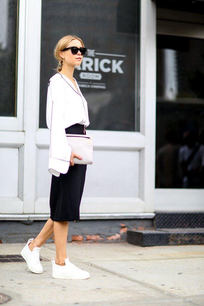 Zwarte koker rok + romantische blouse + witte sneakers + crème clutch.