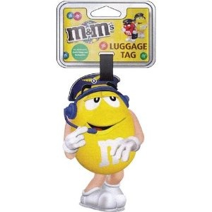 M's Jumbo Luggage Tag - Shown in Yellow    ®/™ M's the letter M and the M's characters are registered trademarks of Mars, Incorporated and its affiliates, ©Mars, Incorporated 2011