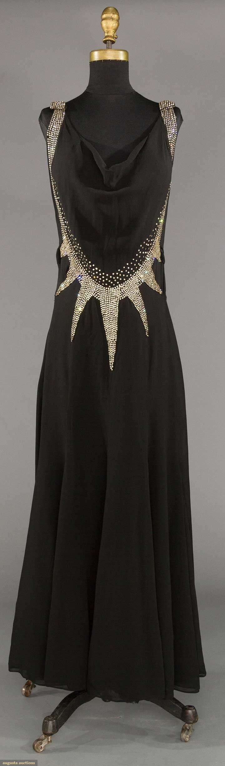 """RHINESTONE DECO EVENING DRESS, 1930s - Lot: 227 May 9, 2017 - CATALOG SALE Sturbridge, Massachusetts - Black silk chiffon w/ wide Deco pattern rhinestone bands, gored skirt, B to 34"""", W to 28"""", H 36"""", (no side opening, couple very small holes to side, large tuck taken in from W to hem seam, 1 tear to chiffon at edge of 1 rhinestone point) fair."""