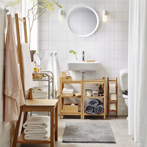A medium size white bathroom with toilet roll stand, shelves and towel rack chair, all in bamboo.