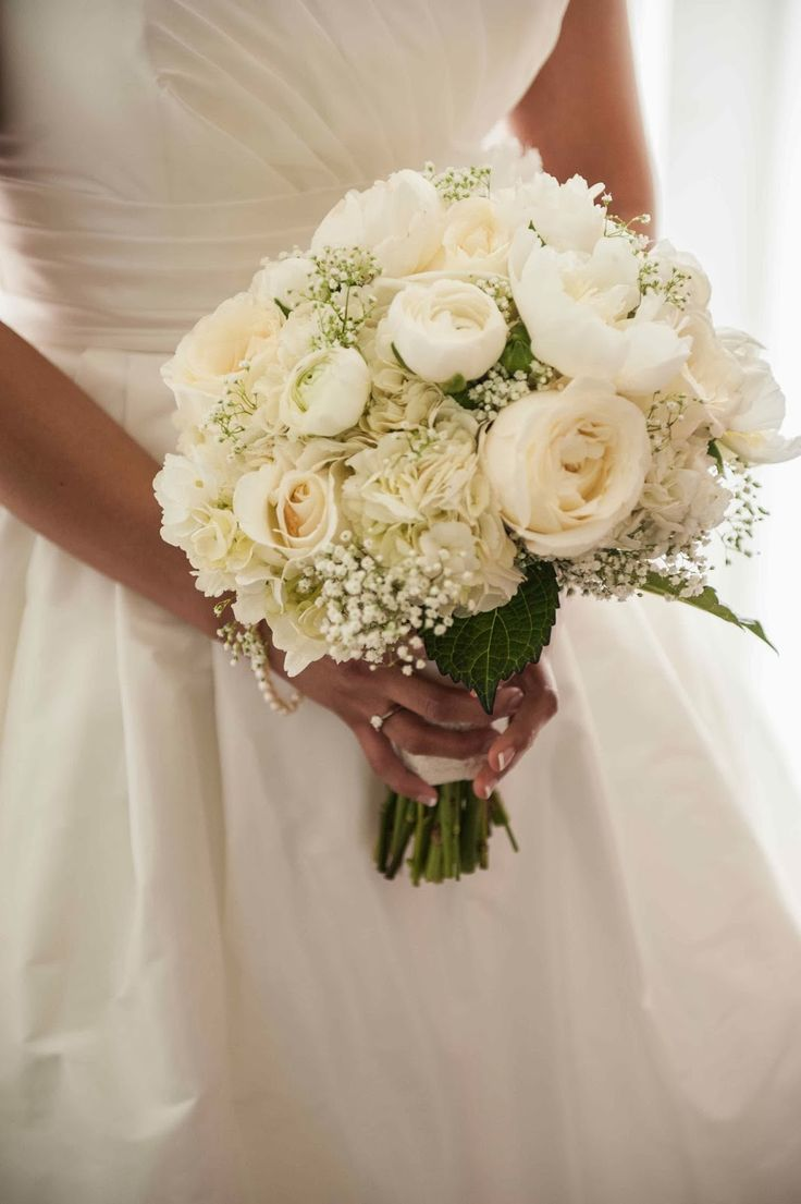 an all white bridal bouquet featuring babies breath peony