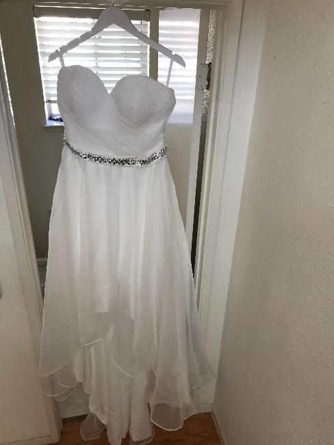 Brand New! Stunning, strapless, organza, high-low wedding gown. Never worn. It's a custom made gown. It's about a US Size 14, with specific measurements (inches): Bust 40, waist 33, hips 45, hollow (collarbone) to floor: 58.5, height 68. Beautifully made of satin covered in organza.