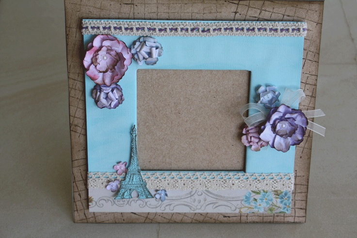 A handmade photo frame measuring 21x21cm. It fits a 10 x 10cm photo. Its made from chipboard and embellished with scrapbooking papers and ribbon.
