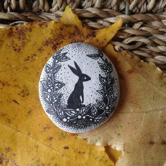 a hand-drawn design, a black rabbit, on a small white stone from a beach in the south of england.  it is approximately 3.5cm across its length and