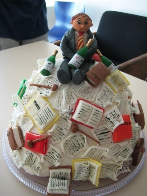 Best law school grad cake ever. notice the pile of books, bottles of booze and the bewildered look on his face!