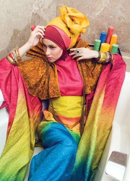 Rainbow tenun wrapped kimono dress with obi, brown songket bolero, maroon Lycra inner hijab, yellow and red tenun scarf worn as headwear, and strand of bangles by Dian Pelangi.