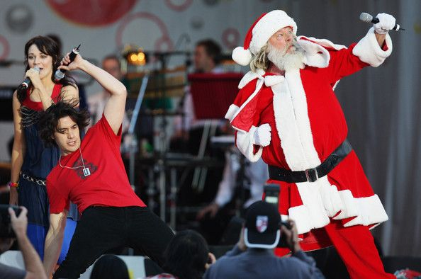 Santa performs some 'crumping' dance moves with Drew Neemia (L) of Sticky TV live on stage during Coca-Cola Christmas In The Park at Aucklan...