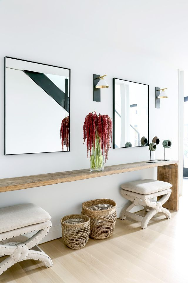 The patina of the timber bench complements the sleek mirror and the modern sconces for a striking contrast.