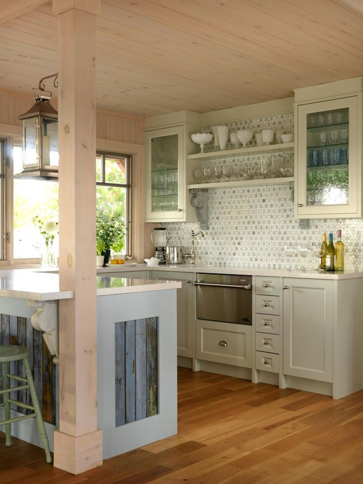 Two long runs of counter space give plenty of room in this cottage kitchen. Blue-painted antique corbels hold open shelving and support the peninsula overhang, bringing vintage-inspired whimsy to the space. Sarah chose three different cabinet colors to create a dynamic color palette. She used natural materials and a lighthearted color for the backsplash, and the seeded glass cabinet doors bring an extra touch of softness.