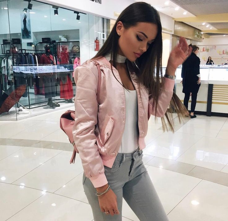 Pretty brunette. Light pink silk bomber jacket with jeans. Winged eyeliner.