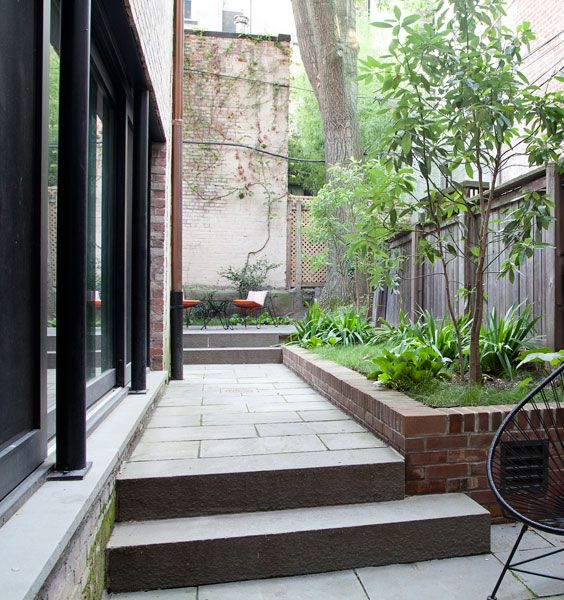 Rear garden of a row house in park slope; elevated brick planters, fence