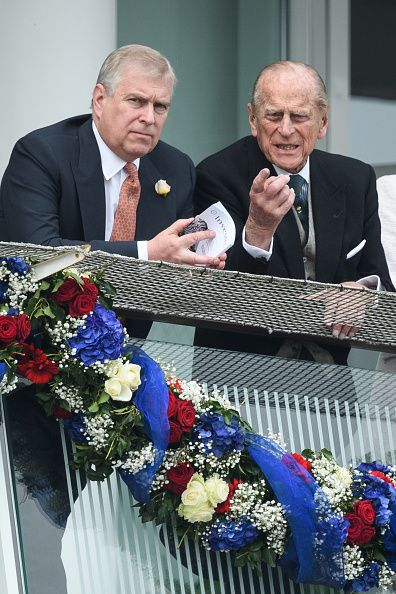 Britain's Prince Andrew (L) talks to his father Prince Philip, Duke of Edinburgh on the second day of the Epsom Derby Festival in Surrey, southern England, on June 4, 2016.
