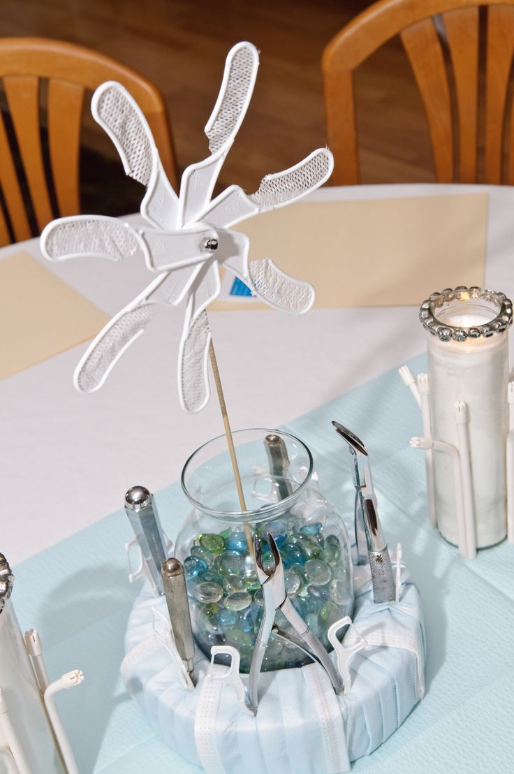Clove Dental created this tablescape for a Hygienist Retirement Party!  Centerpiece was wrapped with dental masks and handpieces and dental floss picks were inserted to complete the look!  Dollar Store candles were rimmed with stainless steel crowns and saliva ejectors were glued around the base.