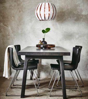 Uma mesa de refeições em preto com cadeiras em pele em castanho escuro e pernas cromadas