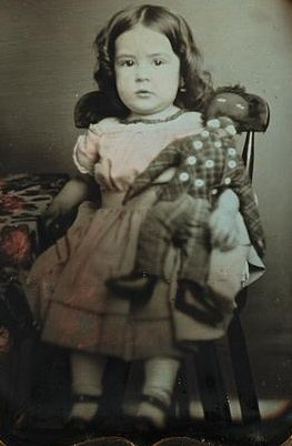 Child seated beside table with table cloth holding a black rag doll