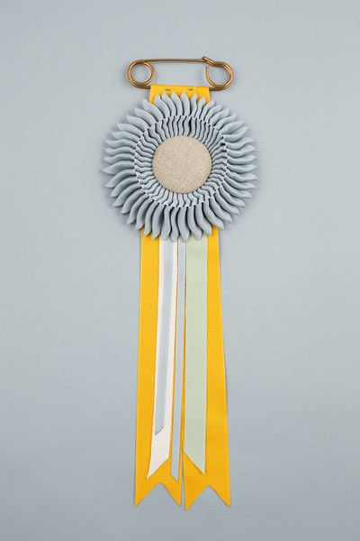 Silver with golden yellow, silver, cream & sage green cotton tails. Natural linen centre. Vintage safety pin.