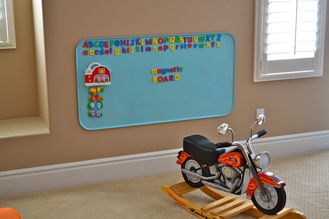 """""""And no playroom is complete without a magnetic board... All you need is a $10 oil drip pan, usually found in the automotive section at Walmart. Since it's not very pretty on it's own, a coat of spray paint dresses it up nicely."""""""