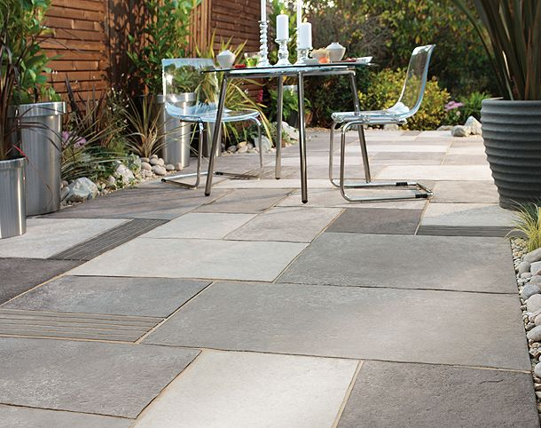 Concrete pavers with various finishes give this patio for Paving stone garden designs