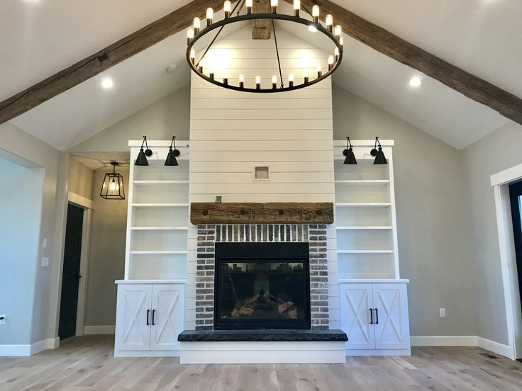 White shiplap fireplace with reclaimed wood mantel, reclaimed bolts and washers and reclaimed bricks from a 1890's building out of Moscow, ID. Reclaimed wood beams, vaulted ceilings and built-in's next to the fireplace. #beanfarm #shiplap #farmhouse #reclaimedwoodbeams