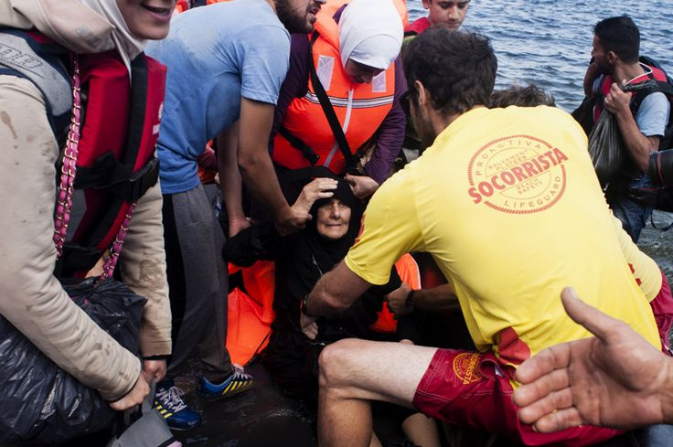 Una anciana es ayudada por un voluntario a bajar de un bote inflable mientras los migrantes y los refugiados llegan a la isla griega de Lesbos, después de cruzar el mar Egeo de Turquía.