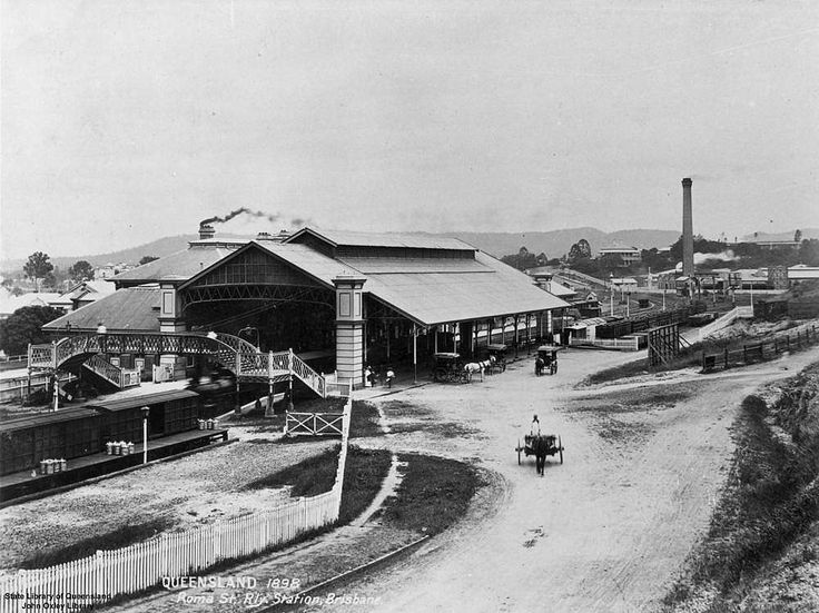Roma Street Railway Station, Brisbane, 1898 - Old Roma Street Station, Brisbane, in 1898, looking south-west. A train is entering the station from the left side of the image. A number of horses and carts are stopped outside the station. People can be seen walking over the pedestrian overpass, and large chimneys are smoking in the background.