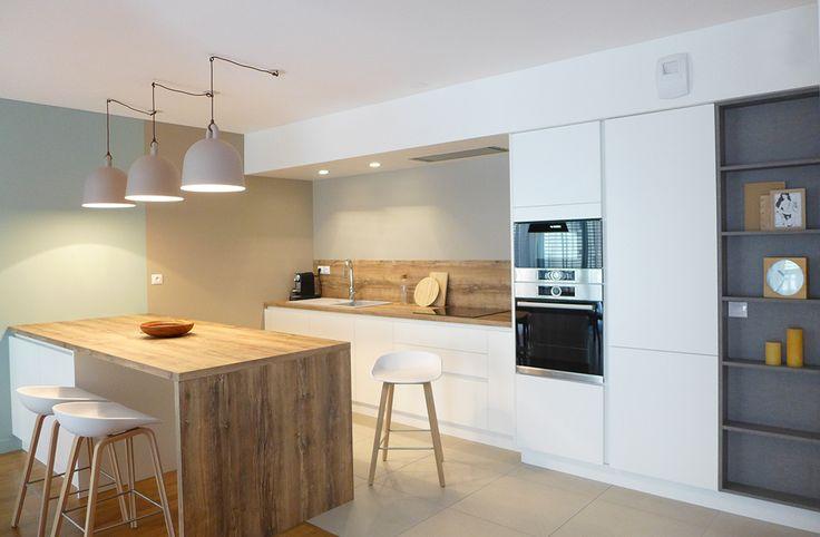 Les suspension Bell ornent l'îlot qui sépare la cuisine du séjour. Les façades sont blanches et les plans de travail en stratifié bois. Dans un style contemporain, cette cuisine est ultra fonctionnelle et design.