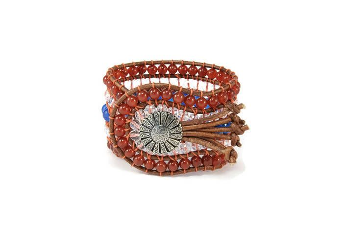 A 5 strands women's bracelet is handcrafted with semi precious stones of carnelian, crystals of high quality & jade blue. All of them are framed by natural brown leather woven together with orange cotton cord. This fabulous design also features a metal, silver, vintage, lightly hammered, details button closure. This statement bracelet pairs beautifully with other silver or gold tone pieces, but can also make a subtle shimmering statement worn alone.