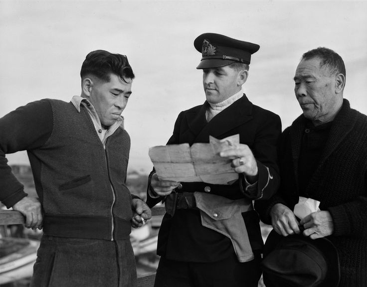 An officer of the Royal Canadian Navy interviews two Canadian fishermen of Japanese ancestry following the confiscation of their fishing boat in British Columbia. In December of 1941, the Canadian government began enacting laws restricting the rights and movement of Japanese-Canadian civilians. On 4 March 1942, regulations under the War Measures Act prevented all citizens of Japanese heritage from remaining on Canada's Pacific coast. Some 22,000 Japanese-Canadians were sent to detention…