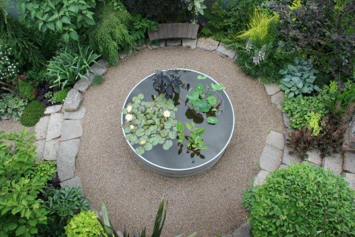galvanized tank makes a striking pond in this circular garden area -gardenista.