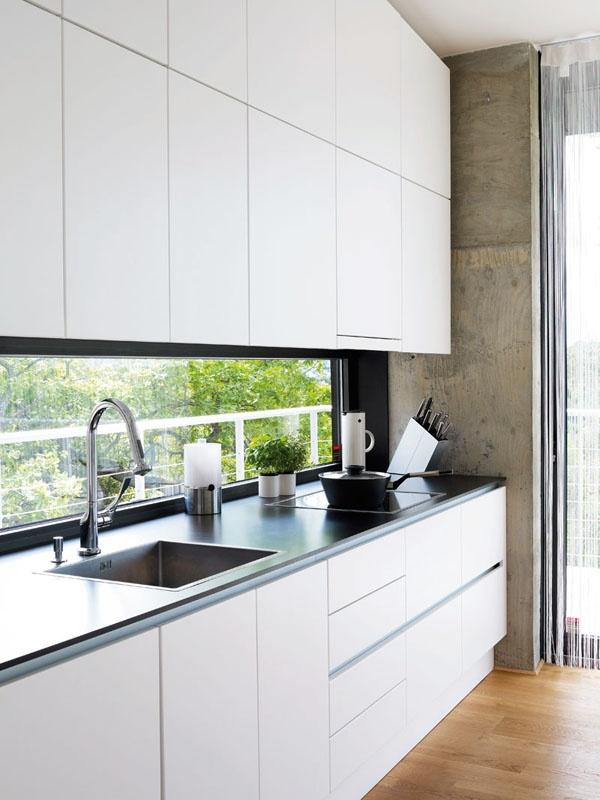 De översta köksluckorna är snedskurna med fem grader för att följa lutningen på taket. En rå betongvägg som lämnats kvar ger en skön kontrast till det vita köket och den svarta arbetsbänken. Kökskranen är en Axor Citterio, från Hansgrohe. Vasken heter Claron och kommer från Blanco Steelart. Termosen kommer från Stelton och knivstället från Eva Solo.