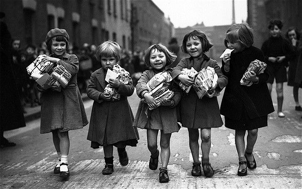 "March 7, 1939: ""Children who are small enough to pass under an archway in Bow, east London, qualify for a weekly parcel of toys. In 1907 the headmistress of Devons Primary School in Bow, Clara Grant, set up a wooden arch on the pavement, inscribed with 'Enter all ye children small, None can come who are too tall'. Any child able to pass through the arch without bending could receive a parcel of toys for a farthing. These parcels quickly became known as Farthing Bundles and Clara Gran"""