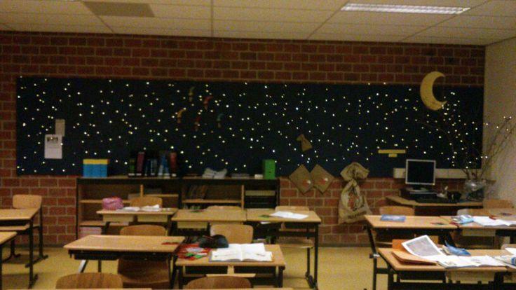 Versiering voor Sint en Kerst in de klas. Lichtjes op een donkerblauw prikbord of op met een zwart doek erachter.