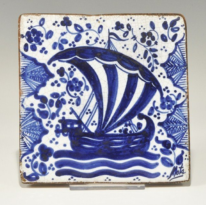 Glazed Ceramic Wall Tile 19th century AD . A tin-glazed ceramic fireplace tile, square in plan, with blue design on a white field depicting a ship under sail with scrolled foliage and pellets, scallop motifs to the edges.