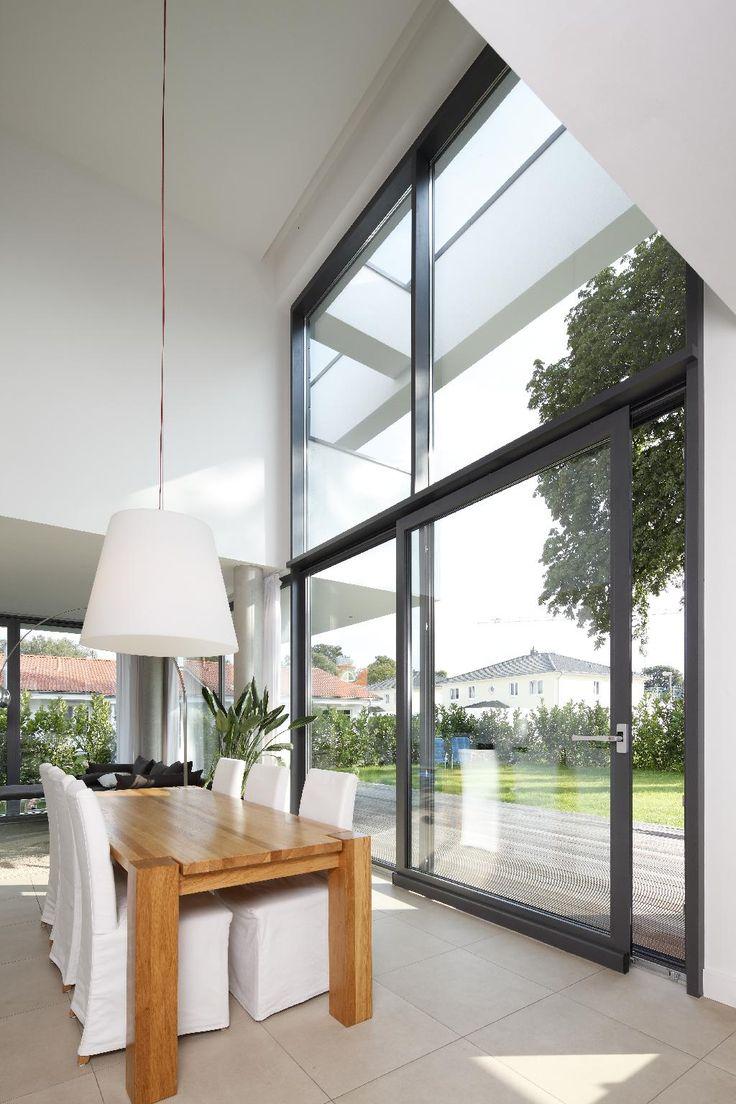Hier moet je op letten wanneer je nieuwe ramen in je bestaande woning of bij het renoveren wil plaatsen. Foto: www.schueco.be (hoge ramen • donker kader • eetkamer • hoog plafond • modern • houten tafel)