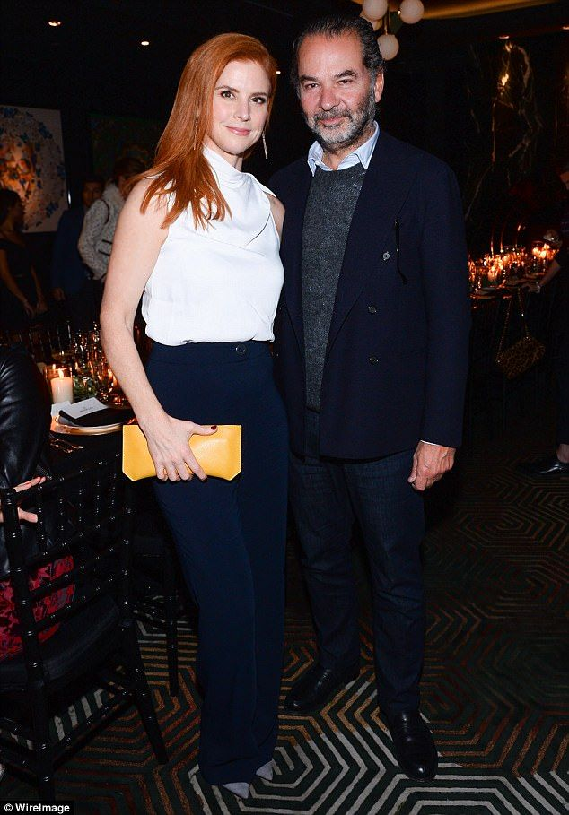 Suits you! Show Sarah Rafferty stunned in a simple white blouse and navy trousers, jazzed up by a bright yellow clutch bag