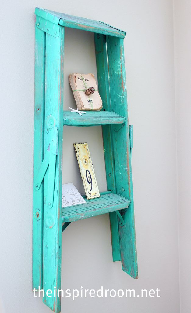 Ladders don't JUST keep us safe. What a wonderful idea with ample wall space and an old step-stool.   Cost friendly. Simple. Chic. Reused.